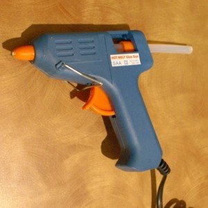 A glue gun will work for gluing small pieces of paper to glass.